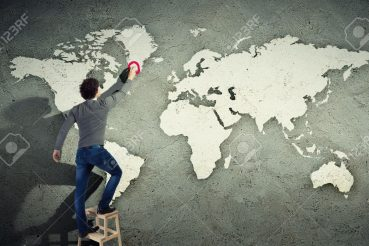 21322326-young-man-drawing-a-world-map-on-the-wall-stock-photo