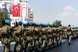 Turkish soldiers march during a parade in the northern part of Nicosia, the capital of the self-proclaimed Turkish Republic of Northern Cyprus (TRNC), on July 20, 2016 to mark the anniversary of of the Turkish invasion of northern Cyprus in 1974.  The anniversary marks the exact moment when Turkish troops invaded in 1974 in response to an Athens-engineered military coup to unite Cyprus with Greece. Flags seen on top left are from Turkey (L) and the one used by the Turkish Republic of Northern Cyprus (R). Portrait seen is of Mustafa Kemal Ataturk, founder of the Republic of Turkey, / AFP / Iakovos Hatzistavrou        (Photo credit should read IAKOVOS HATZISTAVROU/AFP/Getty Images)