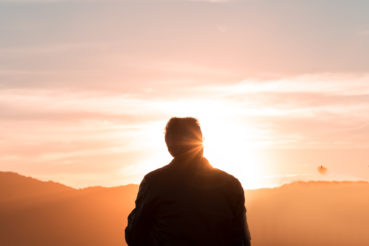 silhouette-of-person-sitting-and-facing-mountain-during-2260959